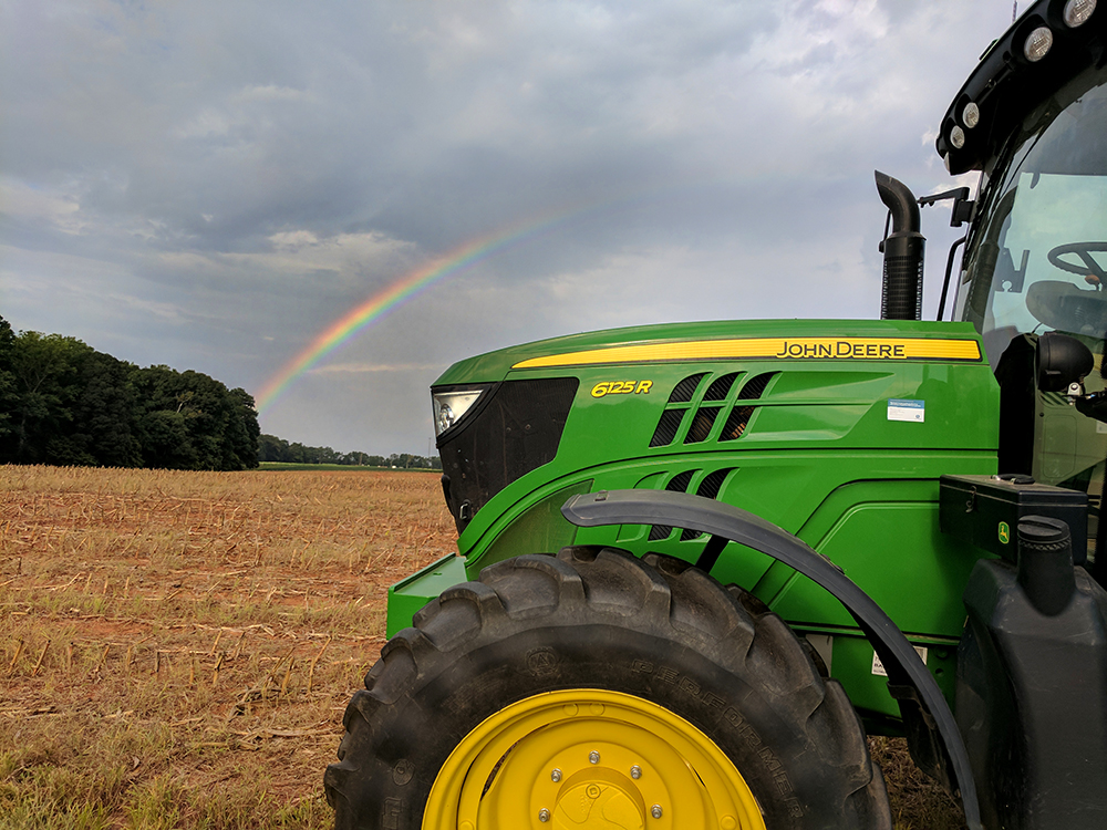 rainbow in background. tractor in foreground