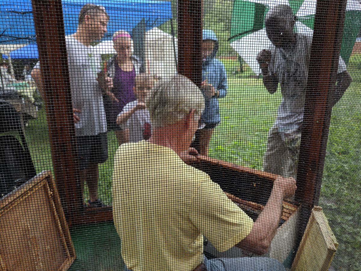 Apiary Inspector Supervisor Don Hopkins does a beekeeping demo in the bee cage.