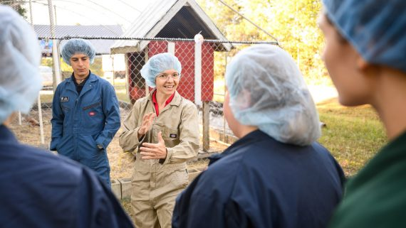Rocio Crespo (center) talks with her students before entering the chicken enclosure.