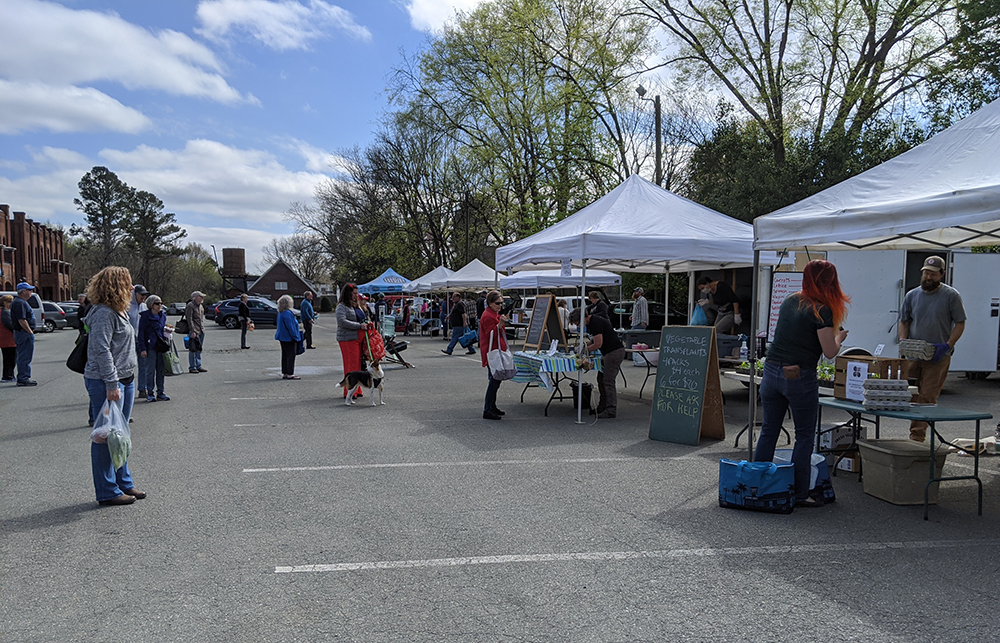 The customers and vendors at the Pittsboro Farmers' Market are spread apart.