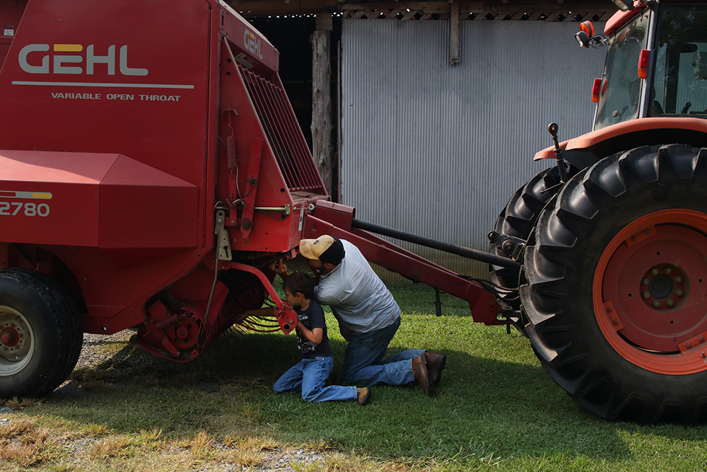 Man looking at hay bailer