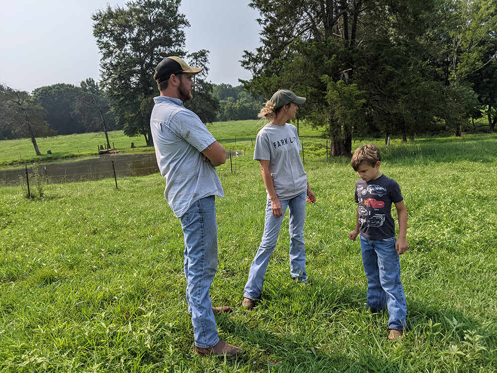 Three people standing in field